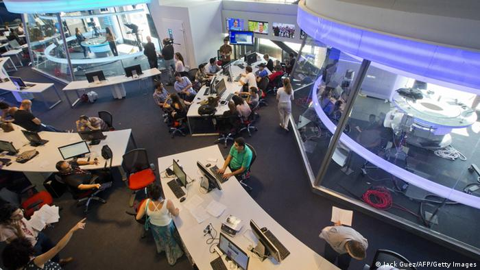 People sit around three different desks in a newsroom (Foto: Jack Guez/AFP/Getty Images)