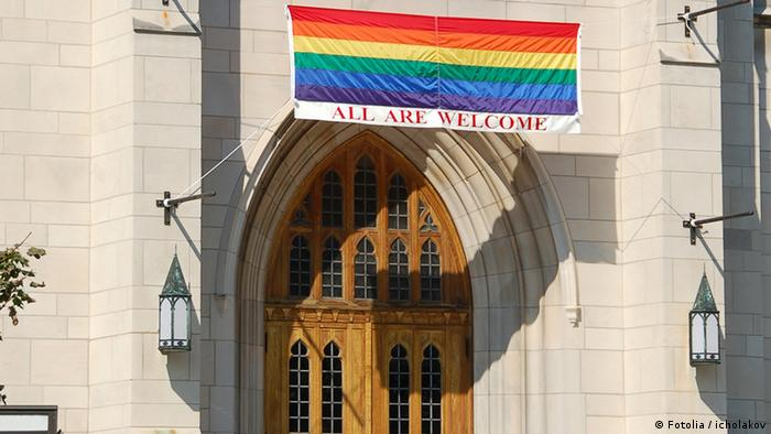 A rainbow flag with and a caption that reads all are welcome is seen on the gate of a church