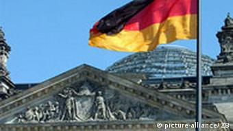 A flag waves in front of the German parliament building