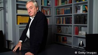 Cees Nooteboom sitzend vor einem Bücherregal.