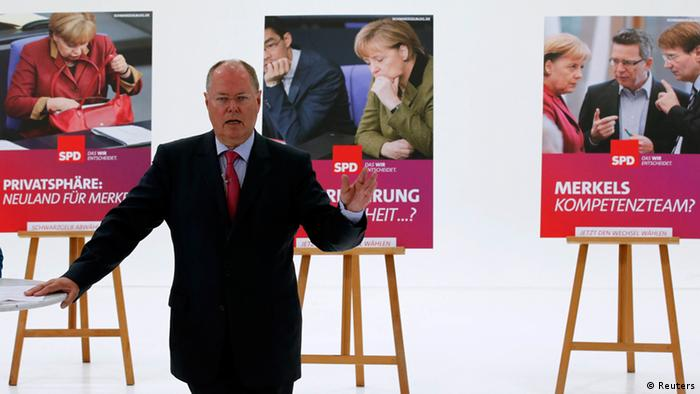 Peer Steinbrueck, the Social Democratic Party's (SPD) candidate for German Chancellor in the upcoming general election, gestures in front of election campaign posters during their official presentation in Berlin July 30, 2013. Germany's main opposition Social Democrats (SPD) launched a poster campaign on Tuesday targeting Chancellor Angela Merkel and her handling of a spying row as the party (showed its desperation by) resorting to negative campaigning before a September 22 election. REUTERS/Fabrizio Bensch (GERMANY - Tags: POLITICS ELECTIONS TPX IMAGES OF THE DAY)