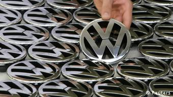 File photo of an employee holding an emblem for a Volkswagen Golf car in a production line at the Volkswagen headquarters in Wolfsburg November 14, 2008. German carmaker Volkswagen said July 31, 2013, that first-half operating profit of its flagship Audi luxury division fell 8 percent to 2.64 billion euros ($3.50 billion) from 2.87 billion a year ago. REUTERS/Christian Charisius/files (GERMANY - Tags: TRANSPORT BUSINESS)