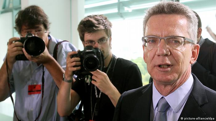 German defense minister Thomas de Maiziere with photographers in background. Photo: Wolfgang Kumm/dpa