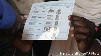 An electoral officer holds up a ballot sheet (AP Photo)