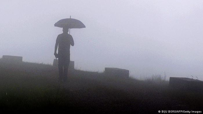 An Indian pedestrian walks through heavy fog at Mawsynram village in the north-eastern Indian state of Meghalaya and considered the wettest place on earth