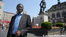 Der aus dem Senegal stammende Karamba Diaby (M) steht am 18.06.2013 auf dem Marktplatz von Halle/Saale (Sachsen-Anhalt). Diaby ist Bundestagskandidat der SPD in Sachsen-Anhalt für den Wahlkreis 72. Diaby wäre der erste in Afrika geborene Abgeordnete im Bundestag, heißt es von der SPD. Der gebürtige Senegalese hat seit zwölf Jahren die deutsche Staatsbürgerschaft, seit 2008 ist er in der SPD und sitzt seit 2009 im Stadtrat von Halle. Foto: Jan Woitas/dpa +++(c) dpa - Bildfunk+++