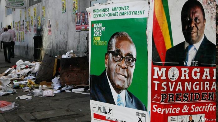 Election campaign posters are pictured near Zimbabweans walking on a street blocked by uncollected garbage in Harare (photo via Reuters)