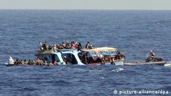 Ein gekentertes Flüchtlingsboot treibt im Mittelmeer. Flüchtlinge halten sich an der Reeling fest und warten auf ihre Rettung durch die Küstenwache (Foto: dpa)