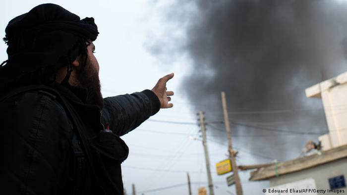 A Rebel fighter points at smoke rising in the city of Aleppo on January 18, 2013. UN leader Ban Ki-moon warned that Syria is in a death spiral, as his top humanitarian and human rights officials pleaded with the UN Security Council to take firmer action. AFP PHOTO / EDOUARD ELIAS (Photo credit should read EDOUARD ELIAS/AFP/Getty Images)