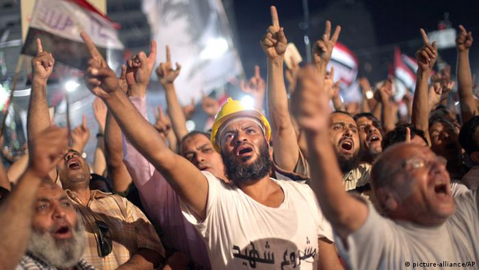 Supporters of Egypt's ousted President Mohammed Morsi chant slogans during a protest outside Rabaah al-Adawiya mosque, where they have installed a camp and hold daily rallies at Nasr City, in Cairo, Egypt, Wednesday, July 31, 2013. Egypt's military-backed government has ordered the police to break up the sit-in protests by supporters of ousted President Mohammed Morsi, saying they pose an unacceptable threat to national security. Information Minister Dorreya Sharaf el-Din said in a televised statement Wednesday that the police are to end the demonstrations within the law and the constitution. The Arabic writing on the white shirt reads A martyr project. (AP Photo/Khalil Hamra) pixel