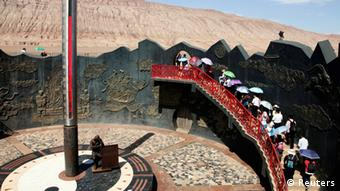 Chinese tourists walk past a huge thermometer near the Flaming Mountain (back) in Turpan, Xinjiang Uighur Autonomous Region, July 30, 2013. The 12-metres (39.4 feet) high thermometer shows the surface temperature of the area which reaches 78 degrees Celsius (172.4 degrees Fahrenheit) on Tuesday. Heat waves continued to scorch many parts of China on Tuesday, triggering level two emergency response to heat from the China Meteorological Administration (CMA), Xinhua News Agency reported. Picture taken July 30, 2013. REUTERS/China Daily (CHINA - Tags: ENVIRONMENT SOCIETY TRAVEL TPX IMAGES OF THE DAY) CHINA OUT. NO COMMERCIAL OR EDITORIAL SALES IN CHINA