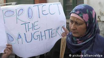 A woman holds a placard: 'Protect our daughters' (Photo: Farooq Khan)