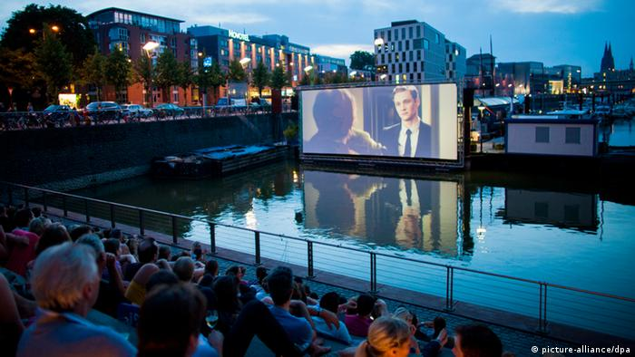 An audience watching a film at the Open Air Cinema at Cologne's Rheinauhafen.