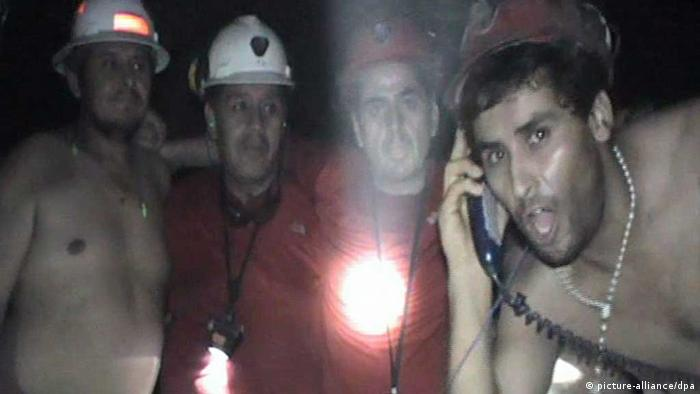 A handout picture provided by the Government of Chile shows a group of trapped miners waving to a video camera at mine San Jose, near Copiapo, Chile, 17 September 2010. Photo: EPA/GOVERNMENT HANDOUT