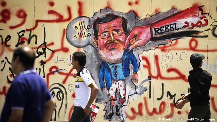 Egyptian protesters walk past graffiti against President Mohamed Morsi on the wall of the presidential palace in Cairo on July 1, 2013. Egypt's opposition gave Islamist Mohamed Morsi a day to quit or face civil disobedience after deadly protests demanded the country's first democratically elected president step down after just a year in office. AFP PHOTO/GIANLUIGI GUERCIA (Photo credit should read GIANLUIGI GUERCIA/AFP/Getty Images)