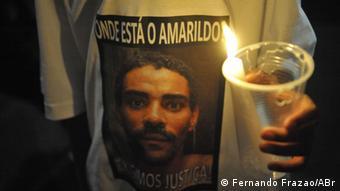Manifestante segura uma vela e veste camiseta com a mensagem Onde está o Amarildo?