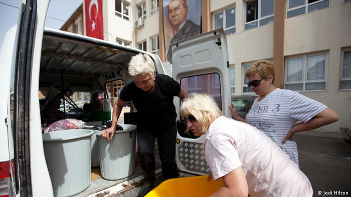 Three female volunteers lift bags of discarded food from a school into a van. Istanbul, Turkey. Mai 2013. Photo: Jodi Hill