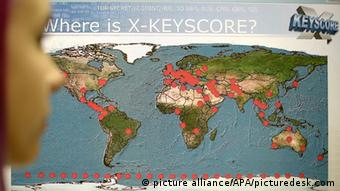 A woman looking at a graphic of XKeyscore locations on a map of the world 