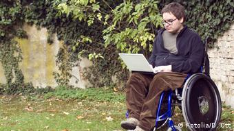 junger Rollstuhlfahrer. Student beim Lernen im Park