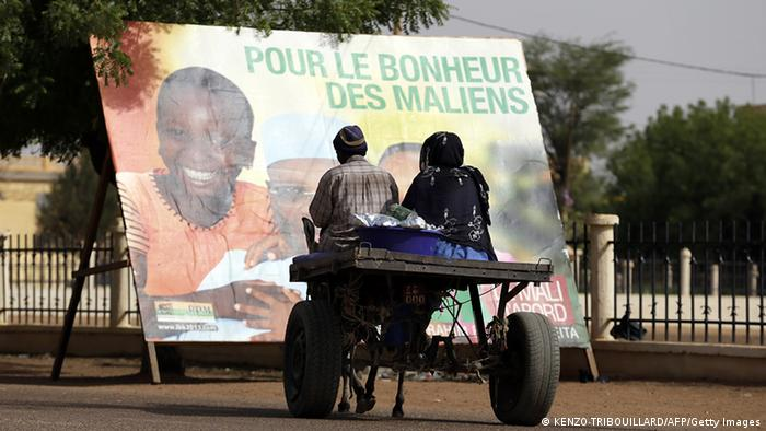Poeple sitting on a cart looking at an election poster ((Photo:KENZO TRIBOUILLARD/AFP/Getty Images)