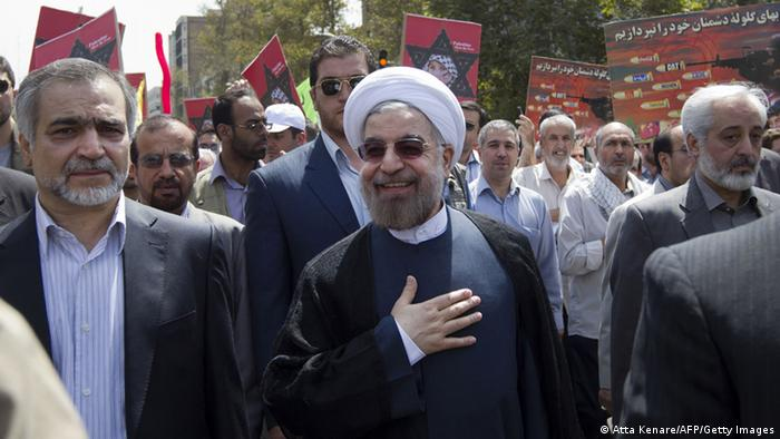 Iranian president-elect Hassan Rowhani (C) takes part in a parade marking Al-Quds (Jerusalem) International Day in Tehran on August 2, 2013. Rowhani said that Israel was a foreign body that must be removed, and also cast doubt on efforts to revive peace talks with the Palestinians. AFP PHOTO/ATTA KENARE (Photo credit should read ATTA KENARE/AFP/Getty Images)