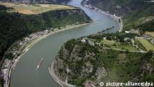 ARCHIV - Das Luftbild vom 26.06.2008 zeigt den Loreleyfelsen bei St. Goar (Rheinland-Pfalz) inmitten des UNESCO-Weltkulturerbegebiets Mittelrheintal. Das Unesco-Welterbe Oberes Mittelrheintal mit seinen Burgen und Weinbergen gilt als Inbegriff der Rhein-Romantik. Unterhalb des Loreley-Felsens, wo der Sage nach einst Fischer ins Verderben gelockt wurden, müssen Schiffer in einem fünf Kilometer langen Abschnitt zwischen Oberwesel und St. Goar auch heute noch eine gefährliche Engstelle passieren. Wegen vieler Kurven und starker Strömungen sind genaue Ortskenntnis und nautische Erfahrung gefordert.(Zu dpa Hintergrund - Der Rhein bei der Loreley - gefährlicher Engpass für Schiffer. Foto: Thomas Frey dpa/lrs +++(c) dpa - Bildfunk+++ pixel