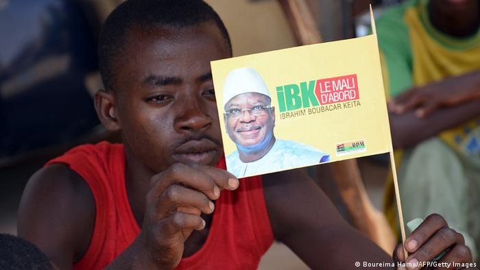 Ein junger Mann hält eine Fahne in der Hand, die den Präsidentschaftskandidaten Keita zeigt. (Foto: Boureima Hama/AFP/Getty Images)