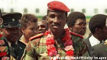 Capitaine Thomas Sankara (C), chef d'Etat de Burkina Faso, arrive le 31 août 1986 à Harare pour le 08e Sommet des Pays non-alignés. Thomas Sankara, le père de la révolution burkinabé, arrivé au pouvoir en août 1983 suite à un coup d'Etat, avait été tué en octobre 1987 avec 12 de ses compagnons lors d'un nouveau putsch sanglant qui a porté au pouvoir son compagnon d'armes, président burkinabé Blaise Compaoré. Captain Thomas Sankara, President of Burkina Faso, arrives 31 August 1986 in Harare for the 8th Summit of Non-aligned countries. Sankara was killed in October 1987 in a coup d'etat in which President Blaise Compaoré, his former comrade-in-arms, took power. In 1983, Compaoré helped his boyhood friend seize power from then President Jean-Baptiste Ouedraogo. (Photo credit should read ALEXANDER JOE/AFP/GettyImages)