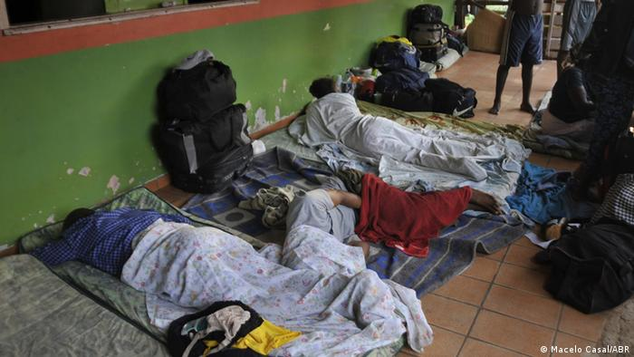 The forms of homeless people in makeshift beds against the green wall of a shop. Photo: Macelo Casal/ABR