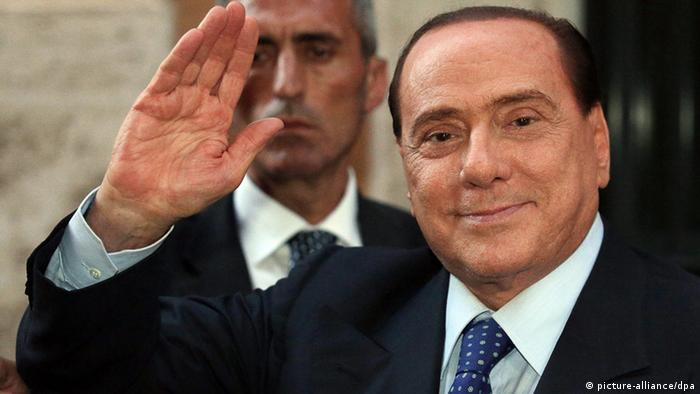 epa03811338 Former Italian Prime Minister Silvio Berlusconi waves after a People of Freedom Party meeting, at the Chamber of Deputies, in Rome, Italy, 02 August 2013. Italy's political leaders appealed for calm on 02 August after a decision by the top court to uphold a jail sentence for Berlusconi on tax fraud charges threatened to throw the fragile governing coalition into crisis. EPA/ANGELO CARCONI