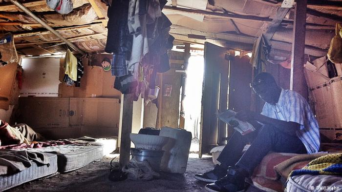 Beschreibung: Ein afrikanischer Einwanderer liest in einer Hütte im Slum nahe der Stadt Foggia. (Foto: Julia Hahn)