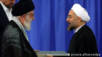 epa03812039 A handout photo made available by Iran's supreme leader website shows Iran's Supreme Leader Ayatollah Ali Khamenei (L) gives the endorsement letter to the new President Hassan Rowhani (R), during a ceremony for his confirmation as Iran's President in Tehran, Iran, 03 August 2013. EPA/IRAN SUPREME LEADER WEBSITE / HANDOUT HANDOUT EDITORIAL USE ONLY/NO SALES