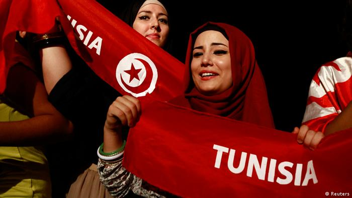 Women holding Tunisian flags take part in a demonstration (c) Reuters