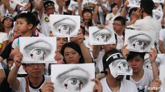 People, holding placards of a bleeding eye, take part in a demonstration in front of the Presidential Office in Taipei August 3, 2013. Hundreds of thousands of demonstrators gathered on Saturday to mourn for soldier Hung Chung-chiu, who died of severe heatstroke after being ordered to do strenuous exercises in a barracks on July 4, and to demand further investigation into Hung's case, according to event organizers. REUTERS/Steven Chen (TAIWAN - Tags: POLITICS MILITARY CIVIL UNREST)