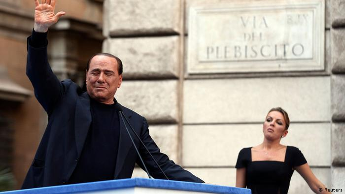 Silvio Berlusconi waves to supporters as his girlfriend Francesca Pascale looks on during a rally in central Rome August 4, 2013.