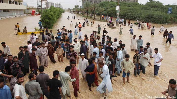 epa03812863 People evacuate flooded areas after heavy downpour in the country's largest city, Karachi, Pakistan, 04 August 2013. At least 70 people were killed in different parts of the country following heavy monsoon rains. EPA/REHAN KHAN