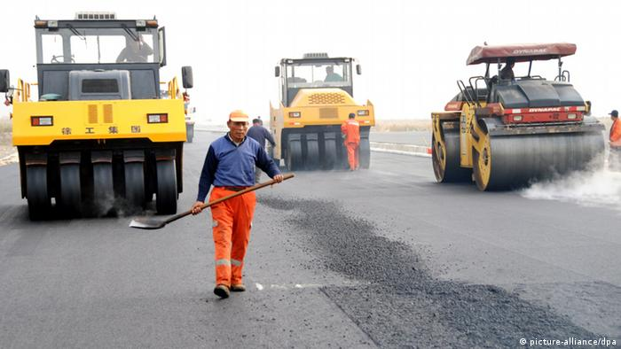 --FILE--Chinese workers pave asphalt on the road surface to build a section of an expressway in Lianyungang city, east Chinas Jiangsu province, 13 November 2010. Chinas road-building has surpassed even its own ambitious plans. The Ministry of Transport said Tuesday (18 January 2011) that construction of twelve national highways has been completed 13 years ahead of schedule. Another eight highways in western China are almost complete, as well, it said. The massive buildup of Chinas highways will soon leave the U.S., the originator of the national highway system, in the dust. Expressways in China now total 74,000 kilometers, or 46,000 miles, the ministry says, just a thousand miles short of the U.S. interstate system, according to U.S. government data. China has said that by 2020, China hopes to have about 85,000 kilometers of national expressways, a target that it will likely reach before the date, since it has already built 90% of the total. Spending on transportation infrastructure has helped power the Chinese economys growth, especially as roads develop local economies and minimize time and effort for trade. And the government is putting money where its mouth is. In the past five years, the Transport Ministry spent 4.7 trillion yuan (US$713 billion) on road and water transportation, more than double the sum of the annual expenditures listed in U.S. Department of Transportations budget reports for the same time period.