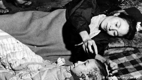 A mother tends her injured child, a victim of the atomic bomb blast at Hiroshima. (Photo by Keystone/Getty Images)