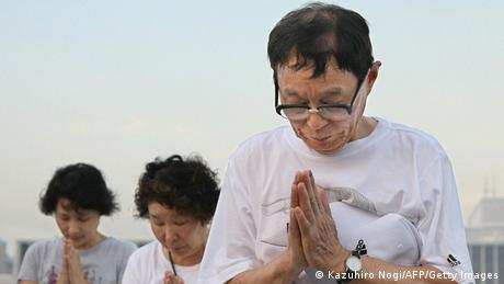 eople pray during the 61st anniversary of the world's first nuclear attack, at the Peace Memorial Park, in Hiroshima, early 06 August 2006. (Photo credit should read KAZUHIRO NOGI/AFP/Getty Images)