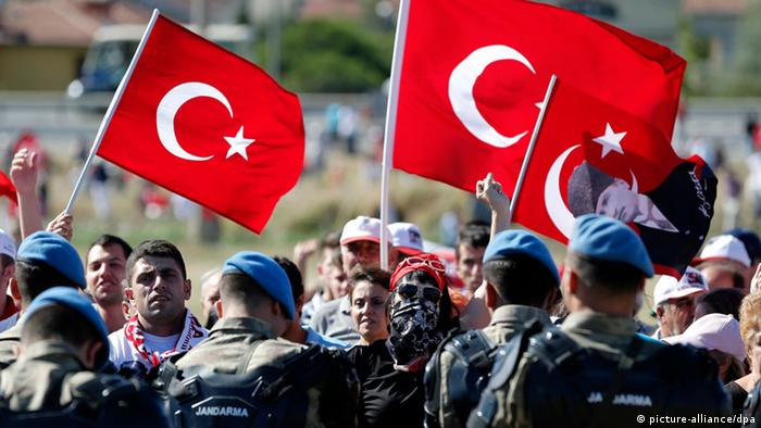 epa03813609 Turkish secular protestors hold Turkish flags and shout slogans against government during a protest as Turkish gendarmes secure the area near the court building in Silivri, near Istanbul, Turkey, 05 August 2013. A Turkish court on 05 August is expected to deliver verdicts against 275 defendants accused of plotting to overthrow the moderate Islamist government of Prime Minister Recep Tayyip Erdogan, media reports said. The defendants include military officers, journalists and academics accused of membership in Ergenekon, a right-wing underground organization that allegedly plotted to destabilize the government and stage a military coup. EPA/TOLGA BOZOGLU FREI FÜR SOCIAL MEDIA