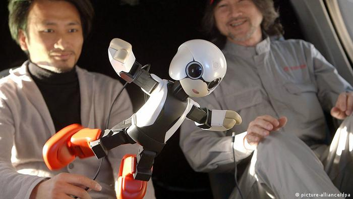 epa03813515 An undated handout image shows Kirobo, a 34cm high talking robot, during a zero-gravity test with robot's developer, Tomotaka Takahashi (L) and Fuminori Kataoka (R), project general manager from Toyota Motor Corp. For the first time in the world on 04 August 2013, Japan launched a talking robot into space towards the International Space Station (ISS) to be employed as 'companion' to Japanese astronaut Kochi Wakata. Kirobo is part of a cargo of drinking water, food and work supplies expected to reach the ISS on 09 August. EPA/2013.KIBO-ROBOT / HANDOUT HANDOUT EDITORIAL USE ONLY/NO SALES