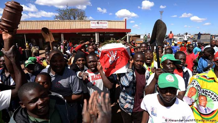 Supporters of Robert Mugabe's ZANU-PF party hold a coffin as they act out the fake funeral of opposition leader Morgan Tsvangirai while celebrating Mugabe's recent election victory in Mbare on August 4, 2013. Zimbabwean President Robert Mugabe was declared the winner of a controversial presidential election with 2,110,434 votes, giving him 61% of the total and his challenger Prime Minister Morgan Tsvangirai 34% amid allegations of blatant vote rigging. AFP PHOTO / ALEXANDER JOE (Photo credit should read ALEXANDER JOE/AFP/Getty Images)