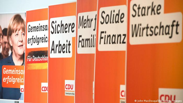 Election campaign placards for the Christian Democratic Party (CDU), featuring German Chancellor Angela Merkel (L), are presented at the CDU headquarters in Berlin
