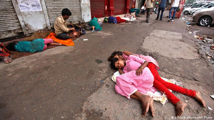 Homeless people sleep outside closed shops in the morning in New Delhi, India, Sunday, July 21, 2013. (AP Photo/ Rajesh Kumar Singh)