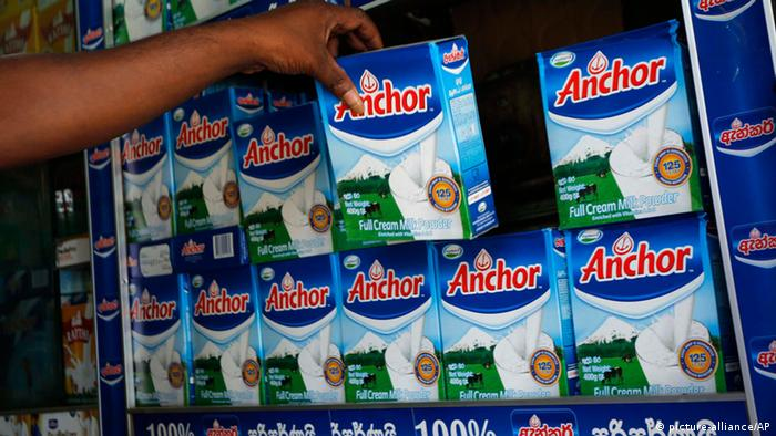 A Sri Lankan shop keeper picks a Fonterra product, which is still displayed for sale in Colombo, Sri Lanka, Tuesday, Aug. 6, 2013. Fonterra, the world's largest dairy exporter, announced Saturday that hundreds of tons of infant formula, sports drinks and other products sold in seven countries could be tainted. On Tuesday, Sri Lanka's health ministry said it had ordered all milk products imported from New Zealand be stopped at ports and the withdrawal of products with whey protein from supermarkets as a precaution after reports of contamination that could cause botulism. (AP Photo/Eranga Jayawardena)