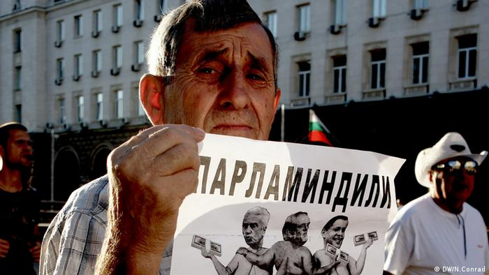 Protestor holds a satirical sign up in Sofia outside the government building. (Photo: Naomi Conrad, DW Correspondent)