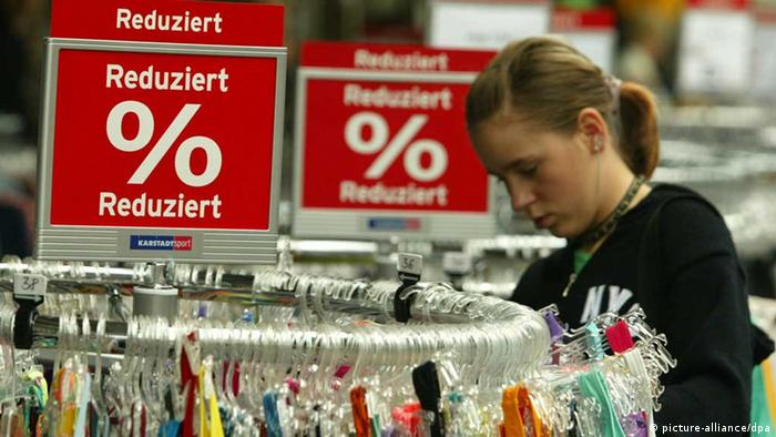 A woman looks through clothes at a shopping center in Germany