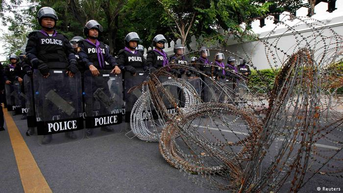 Thai riot policemen stand guard behind a barricade outside parliament in preparation for anti-government protests in Bangkok August 7, 2013. (Photo: Reuters)