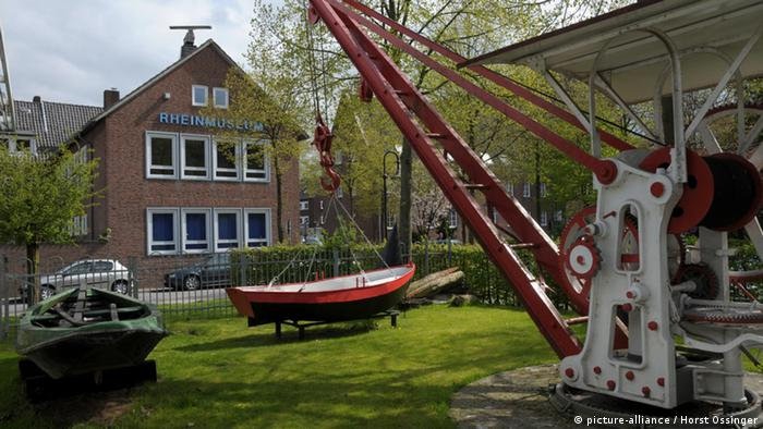A red rowboat attached to a crane outside the Emmerich Rhine Museum.