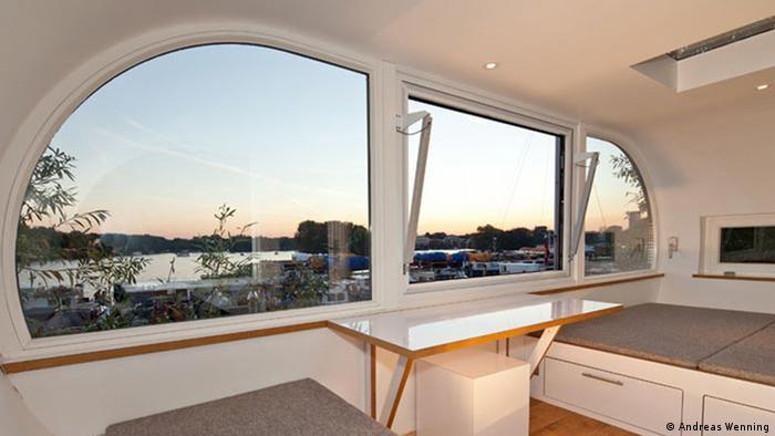 Baumhaus direkt an der Spree in Berlin realisiert. Der Innenraum ist weitgehend mit weiß beschichteten Werkstoffen gestaltet. Durch die großen Glasflächen hat man einen traumhaften Blick auf einen kleinen Hafen und vorbeifahrende Boote auf der Spree. Fotograf: Markus Bollen